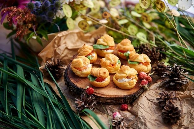 Профитроли с мягким сыром, красной рыбой и зеленью. изысканная еда для праздничного стола.