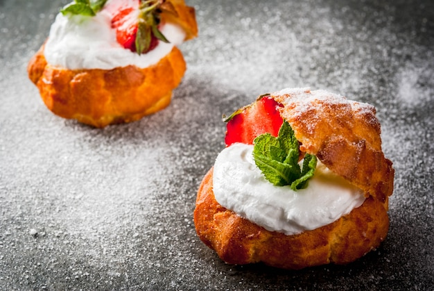 Profiteroles with whipped cream, strawberries and mint