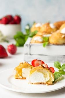 Profiteroles(シューアララクリーム)-カッテージチーズとクリーム、イチゴ、ミント、コーヒーカップを添えたフランスのシューペストリーボール。