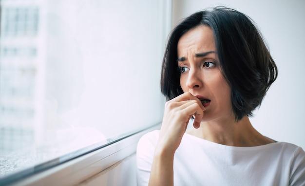 Глубокий стресс. крупным планом фото грустной женщины, которая смотрит в окно и кусает ногти в беде.
