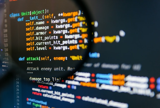 Программный код на дисплее компьютера в увеличительном стекле. крупный план