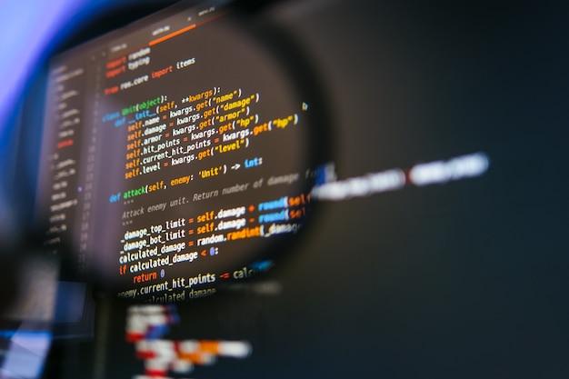 虫眼鏡のコンピュータディスプレイ上のプログラムコード。閉じる
