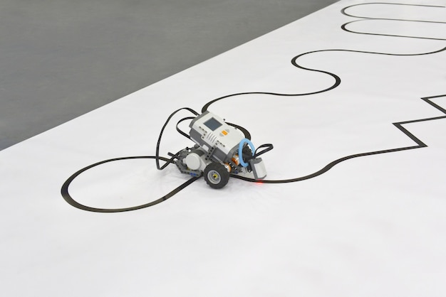 ラインフォロー機能を備えたプログラム可能な4輪ロボットカー。クリッピングパスと白い背景の上の線を運転するロボット