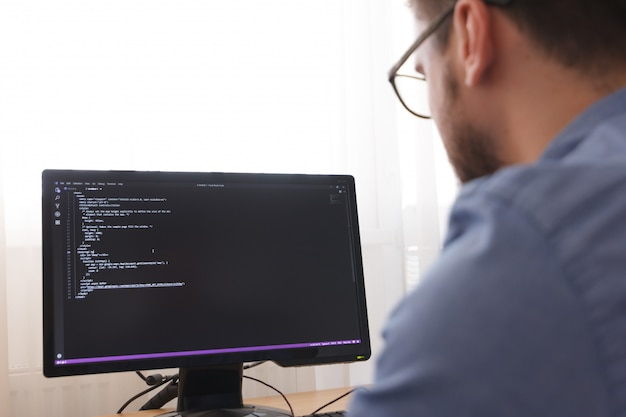 Programmer in glsses typing new lines of html code. web design business and web development concept. freelance work, los angeles, california - 25.10.2019