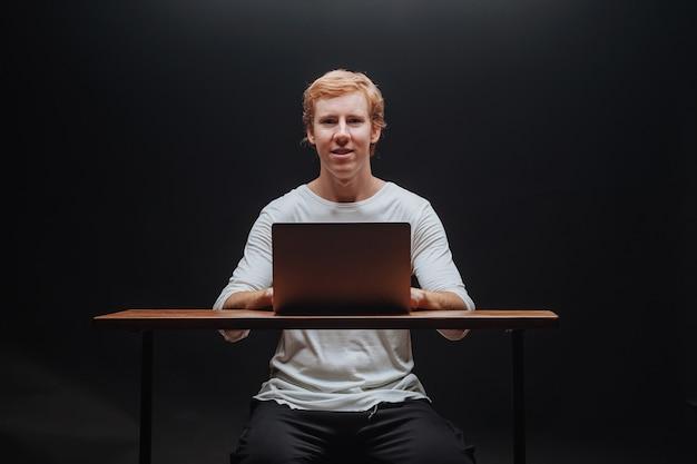 Программист в белой футболке на черном фоне с ноутбуком