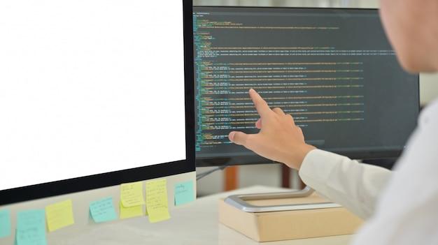 プログラマーがデータをチェックしています。彼はコンピューターの画面を指差しました。