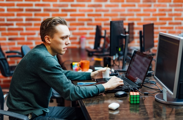 Programmer sitting at a desk with modern technologies and thinking developing programming. man working in a software develop companyfice, writing codes and typing data code.