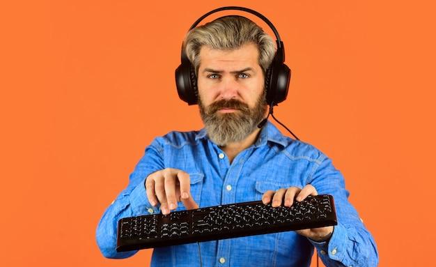 키보드에 입력하는 프로그래머. 디지털 음악 제작. 남자는 헤드폰과 키보드를 듣습니다. 통신 개념입니다. 지원, 콜 센터 및 고객 서비스 헬프 데스크. 컴퓨터 게임을 하는 게이머.