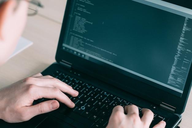 Programmer writing code on laptop keyboard