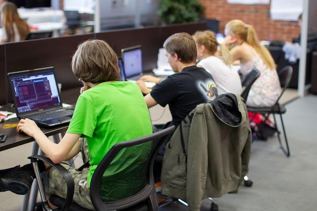 仕事中のプログラマー。若い男はコンピューターで働いています