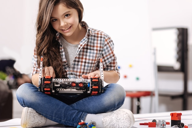 デジタル玩具のプログラミング。ロボット工学研究室に座って、それをプログラミングしながらデジタルロボットを保持している喜んで熟練した才能のある女の子