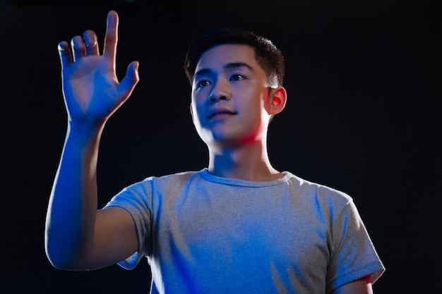 進歩的な時代。透明な画面の前に立っている間、現代の技術を使用して素敵なアジア人