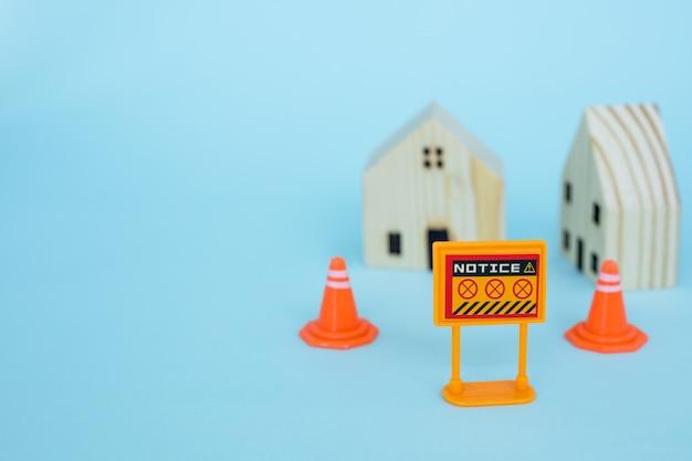 自己検疫とコロナウイルスやcovid-2019状況の概念で家にいるための青色の背景にぼやけた木造住宅モデルの禁止標識