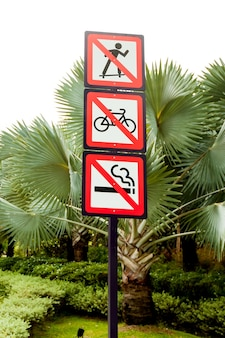 Prohibition signs in the park. not to skate, smoke, bike.