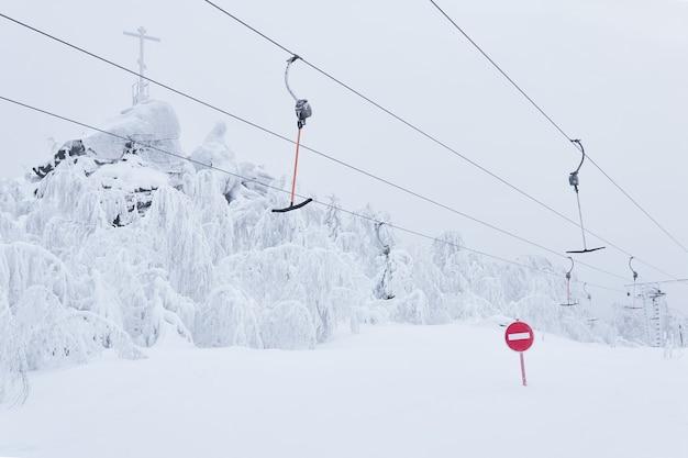 금지 도로 표지판 눈 덮인 스키 슬로프에서 빈 스키 t-바 표면 리프트의 배경에 대한 진입 금지