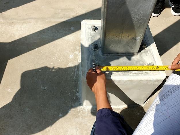 Инженер-проектировщик перепроверяет болты соединения опорной плиты стальной конструкции навеса для солнечных батарей