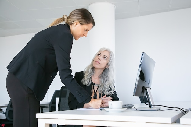 Project manager affixing signature on employees report. female business colleagues sitting and standing at workplace with monitor and coffee cup. business communication concept