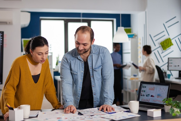 프로젝트 관리자와 조수가 새로운 비즈니스를 위한 차트에서 함께 작업합니다. 컴퓨터에서 회사 재무 보고서를 분석하는 다양한 기업인 팀.