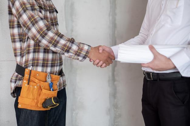 プロジェクトマネージャーと職長は、プロジェクト建設現場での成功のために握手を交わしています