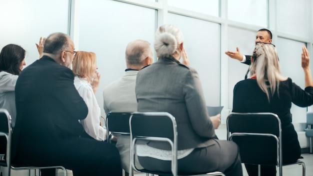 会議中に従業員からの質問に答えるプロジェクトマネージャー