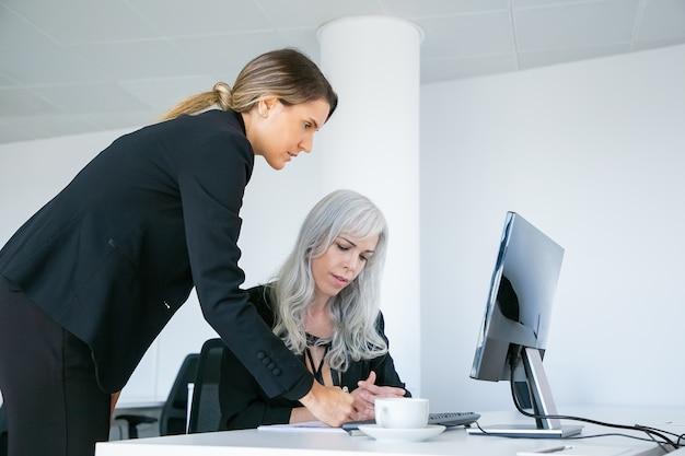 プロジェクトマネージャーは、従業員のドキュメントに書き込み、モニターでプロジェクトのプレゼンテーションを確認します。一緒に職場に座って立っている女性の同僚。ビジネスコミュニケーションの概念