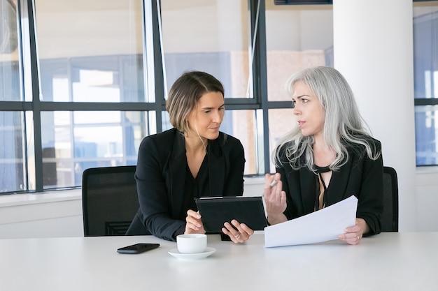 보고서를 분석하는 프로젝트 관리자. 함께 앉아, 문서를 찾고, 태블릿을 사용하고 이야기 두 여성 비즈니스 동료. 전면보기. 통신 개념