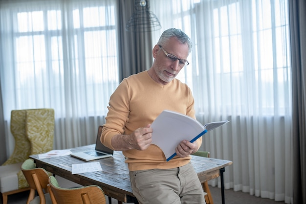 Project papers. gray-haired man in eyewear looking busy while working with project papers