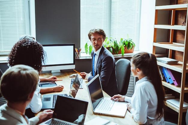 Презентация проекта в конференц-зале, глядя на белый экран, коллеги собираются вместе, обсуждают финансовую статистику