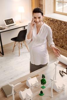 Реализация проекта. вид сверху веселого очаровательного беременного дизайнера, стоящего всего лишь за столом, жестикулируя и улыбаясь