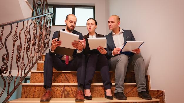 残業をしている金融プロジェクトを説明する階段に座っている文書を見ているビジネスワーカーのプロジェクトチーム。職場の忙しい階段で会社のマネージャーとオフィスエグゼクティブのグループ。