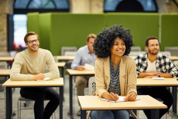 Группа подготовки команды проекта молодых счастливых многорасовых людей, сидящих за столами в современном