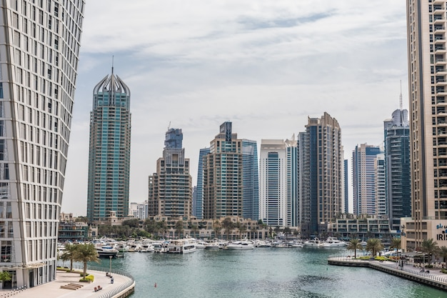 Promenade and canal in dubai marina with luxury skyscrapers around, united arab emirates
