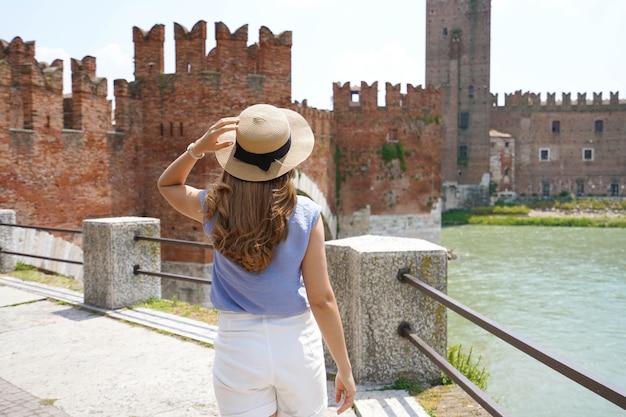 イタリア、ヴェローナの遊歩道の川沿い。中世の要塞カステルヴェッキオ城と橋を背景に遊歩道を歩いている女性の背面図。