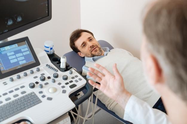 환자가 의료용 침대에 누워주의 깊게 듣고있는 동안 환자를 설명하는 저명한 성숙한 현지 전문가
