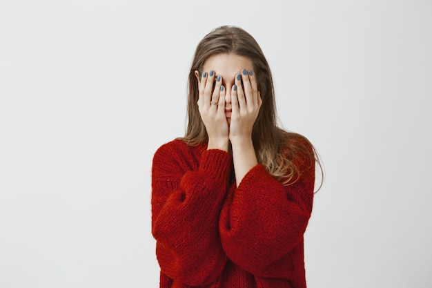 Prometto, non sto sbirciando. colpo di donna attraente stanca e stufo in maglione allentato rosso, che copre il viso con i palmi delle mani, sentendosi stressato ed esausto, avendo bisogno di rilassarsi e dormire sul muro grigio