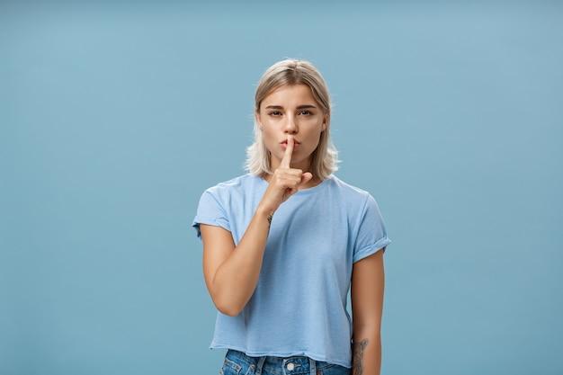 誰にも秘密を教えないことを約束します。日焼けした肌と入れ墨のある神秘的な魅力的でフェミニンなブロンドの女性は、青い壁に何かを隠しているかのように人差し指で目を細めています。