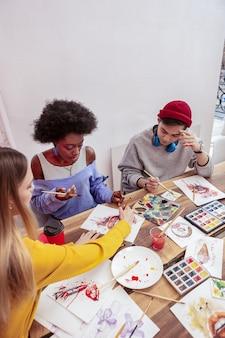 有望なアーティスト。一緒に描くことに関与していると感じている3人の若い有望なアーティストの上面図