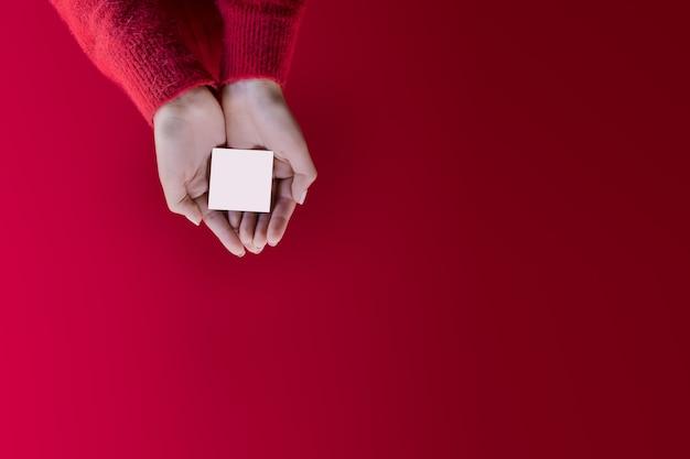 プロモーションテンプレートクリスマスカード赤い背景にカスタマイズ可能な空のスペースを持つ女性の手