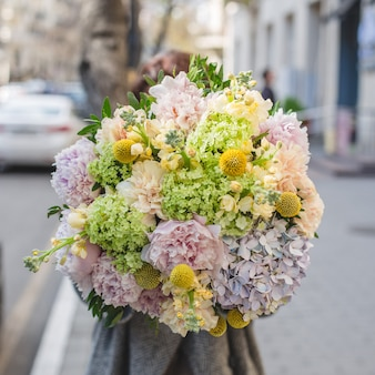 Promoting a mixed flower bouquet in the street.