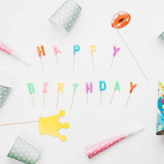 Prop; party horn and party hat around the happy birthday candles against white background