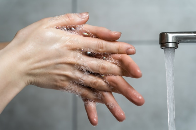 Proper hand washing. woman washes hands with soap under running water