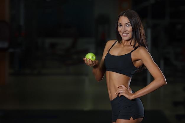Концепция правильного питания, стройная спортсменка с яблоком в руке. здоровое питание и спорт, правильный выбор образа жизни