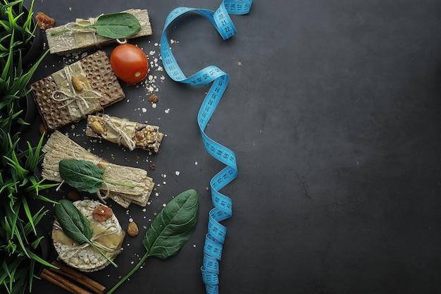 適切な栄養。健康的な生活様式。ダイエット用の乾燥ロールパン。減量と健康的なライフスタイルの概念。テーブルの上に野菜とハーブが入ったロールパン。