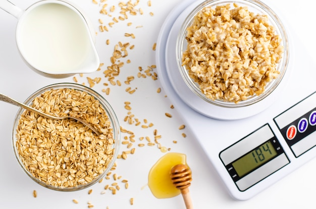 Proper nutrition menu for breakfast with oatmeal porridge on digital kitchen scales, milk and honey