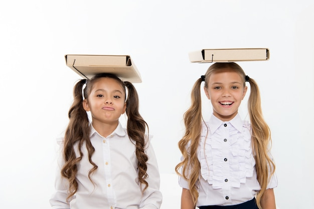 Proper posture. schoolgirls with cute pony tails hairstyle carry folders on heads. perfect schoolgirls with tidy fancy hair and proper posture carry folders on heads. balance and burden of knowledge.