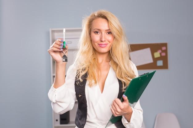 Концепция собственности - молодой агент по недвижимости, держащий ключи.