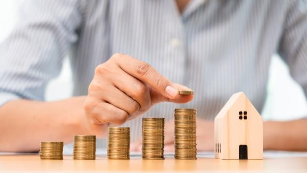 Финансовая концепция инвестиций в недвижимость и ипотеки, рука бизнесмена, который складывает монеты для инвестиций в недвижимость, сбережений для покупки жилья или спекуляции.