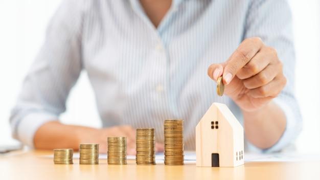 부동산 투자 및 주택 모기지 금융 개념, 부동산 투자를 위해 동전을 쌓아 두는 사업가의 손, 주택 또는 투기 구매를 위해 저축합니다.
