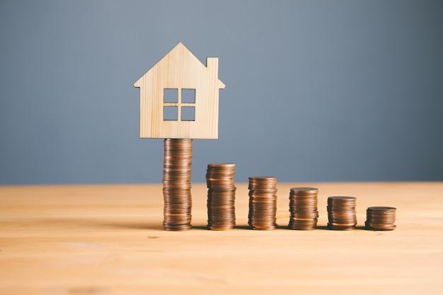 Финансовая концепция инвестиций в недвижимость и ипотеки, денежная монета с деревянным домом
