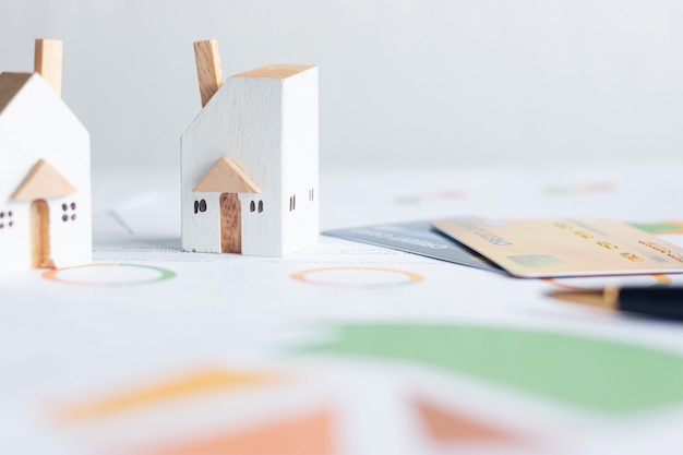 Property investment, miniature white houses with credit cards and  financial documents on table
